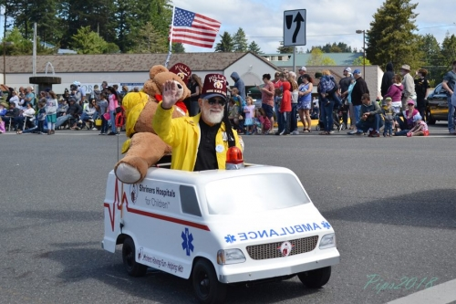 Gentleman riding in mini ambulance with teddy bear on the Azalea Parade Route