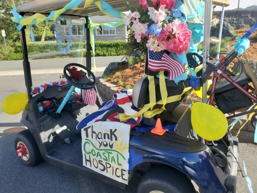 Decked out Golf cart with American Flags and a Thank you to Coastal Hospice
