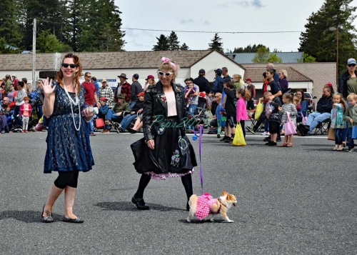 Ladies dressed up the 70s decade waving and walking a dog down the Azalea Parade Route