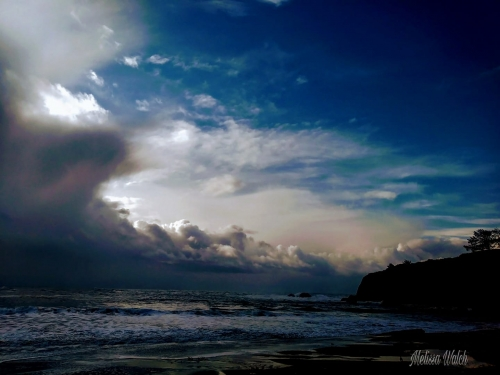 big white clouds in the shape of waves over the pacific ocean in brookings oregon