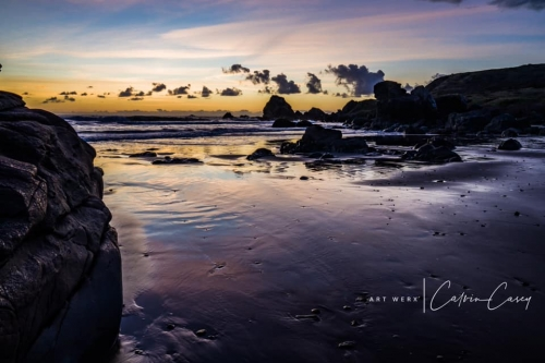 purple and blue sunset reflecting over the ocean and wet sand with clouds and rock formations