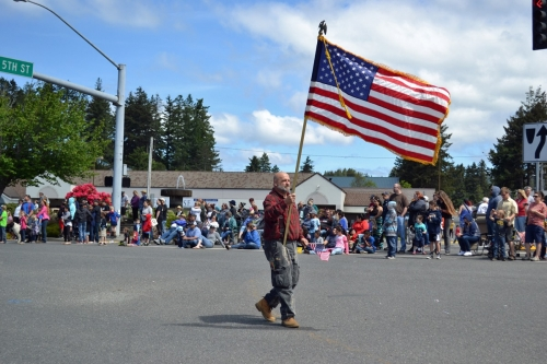 Gentleman carries large American Flag for the crowd at the Azalea Parade