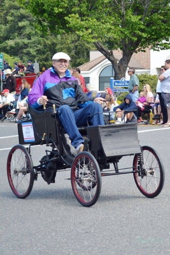 Guy riding a unique bicycle wearing white hat and smiling down the Azalea Parade route