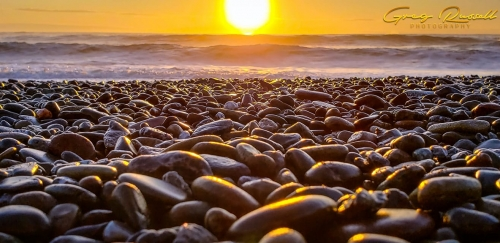 close up of pebbles along the coastline with sun setting over the ocean in the background