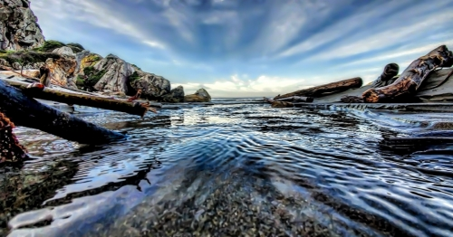 close up of creek running into the ocean with driftwood along the side of the creek, rock formations and moving clouds on a blue sky background