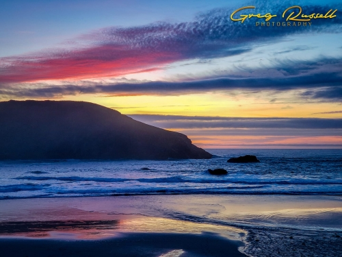 pink purple yellow and blue sunset over an ocean rock formation and reflecting off of the water and wet sand
