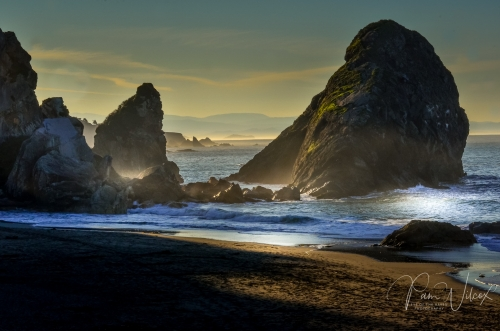 glowing ocean scene with large rock formations sandy beaches and blue waves crashing against rocks