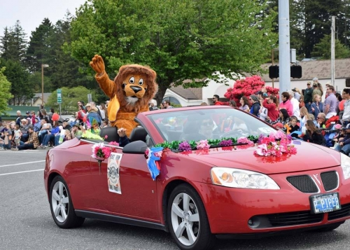 lion in a red convertible Pontiac waving to crowd as it drives down the Azalea Parade route