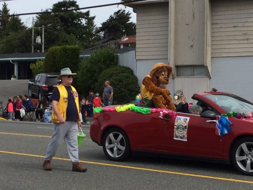 lion in red Pontiac convertible car waving, man in yellow vest walking along side during the Azalea Parade route