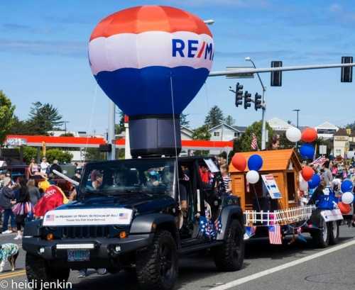 Giant Re-max Balloon attached to a black jeep, followed by tiny home parade float with red white and blue balloons