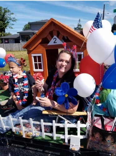 Remax lady and little girl smiling in front of tiny home float with red white and blue balloons, flowers and bead necklaces