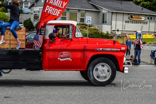 Red Chevy Truck from Gold Beach Lumber with a Family Pride Banner and American flag going down Azalea Parade route