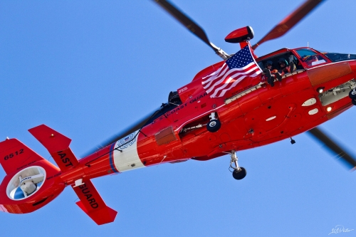 Red Coast Guard helicopter flying over head and waving an American Flag