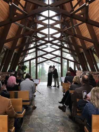 couple kissing during wedding ceremony at the capella by the sea in brookings at azalea park