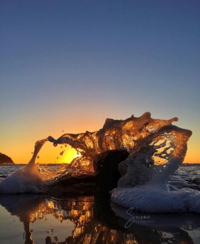 Huge splash as wave crashes into rock, reflection of splash in the water with an orange fiery sunset behind the rock