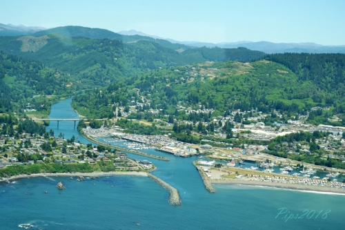 view from helicopter of the port of brookings-harbor, green and blue ocean and the chetco river feeding into the ocean