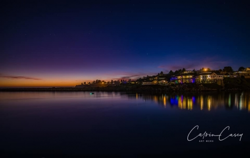 night view of the north jetty beach, stars and orange sunset in the background, houses with colorful lights overlooking the river