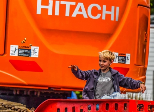 Little boy with blinde hair standing on Hitachi machine throwing candy into the crowd at the Azalea Parade