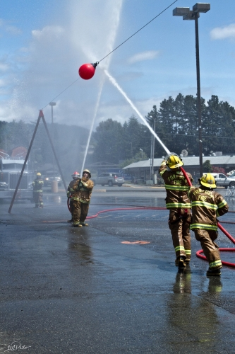 local firefighters spraying their hoses at a red weight ball to try and see who can win the competition at the azalea festival