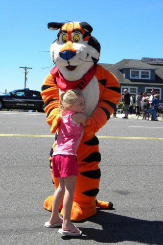 Little girl wearing a pink outfit and giving a big hug on the street to the Tony the Tiger dress up during the Azalea Parade